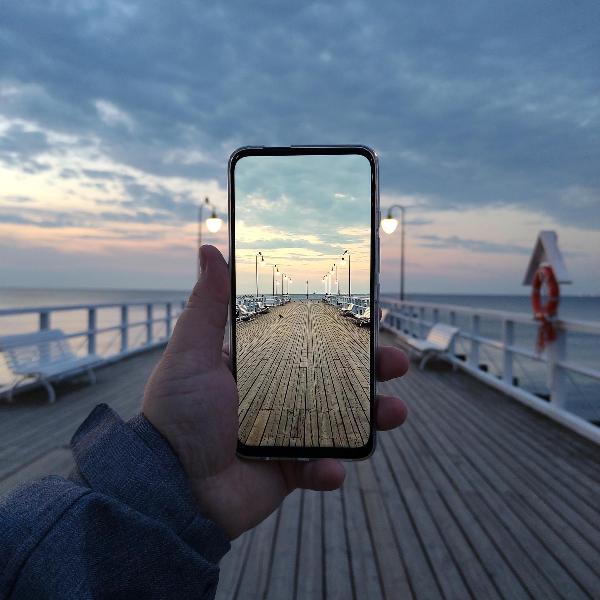 Zdjęcie zPoradnika Fotografii Mobilnej przedstawia rękę trzymającą smartfon Motorola One Fusion Plus natle wschodu słońca namolo wGdyni Orłowie. Naekranie telefonu jest zdjęcie przedstawiające tosamo molo takzeskalowane, żetworzy ztłem jedną całość.