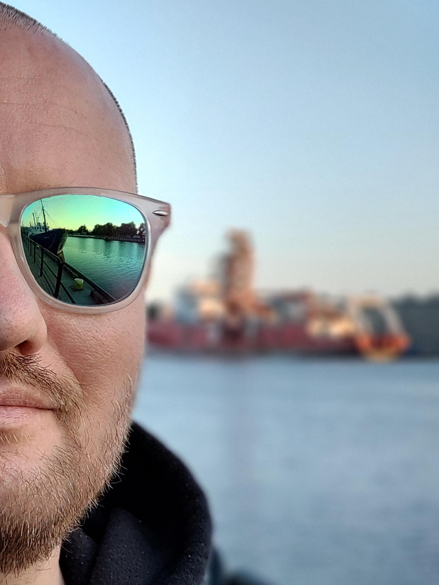 Portret mężczyzny, pół twarzy irozmyte morze iGdynia wtle.